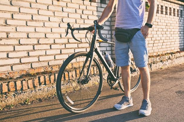 Le jeune homme à vélo marche sur la route