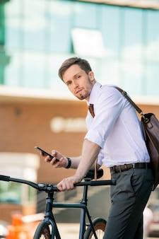 Jeune homme à vélo et smartphone vous regarde en se tenant debout sur fond de centre d'affaires moderne