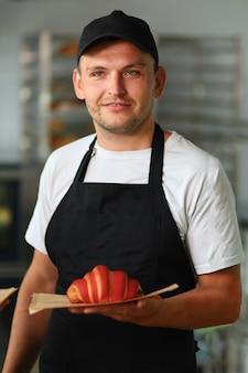Jeune homme vendeur et travailleur au café et boulangerie tenant un croissant