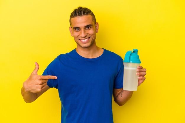 Jeune homme vénézuélien buvant un shake protéiné isolé sur fond jaune personne pointant à la main vers un espace de copie de chemise, fier et confiant