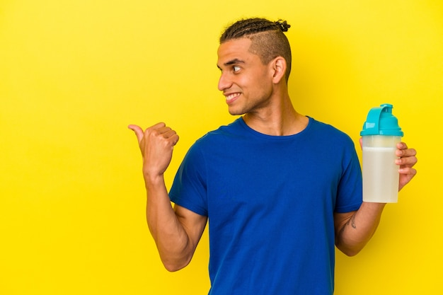 Jeune homme vénézuélien buvant un shake protéiné isolé sur des points de fond jaune avec le pouce loin, riant et insouciant.