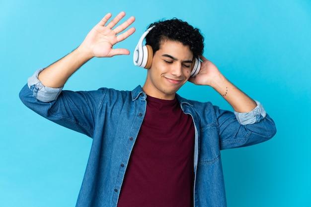 Jeune homme vénézuélien isolé sur bleu écoute de la musique et de la danse