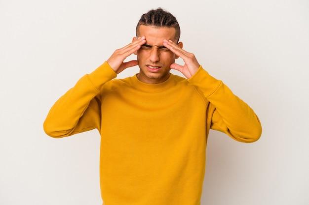 Jeune homme vénézuélien isolé sur fond blanc ayant un mal de tête, touchant le devant du visage.