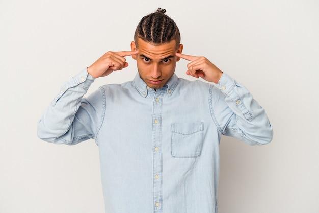 Jeune homme vénézuélien isolé sur fond blanc concentré sur une tâche, gardant les index pointant la tête.