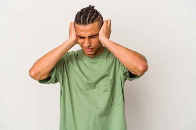 Jeune homme vénézuélien isolé sur fond blanc couvrant les oreilles avec les mains.