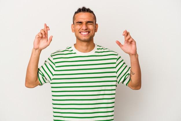 Jeune homme vénézuélien isolé sur fond blanc croisant les doigts pour avoir de la chance