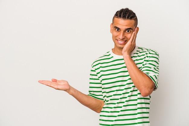 Jeune homme vénézuélien isolé sur fond blanc détient un espace de copie sur une paume, garde la main sur la joue. émerveillé et ravi.