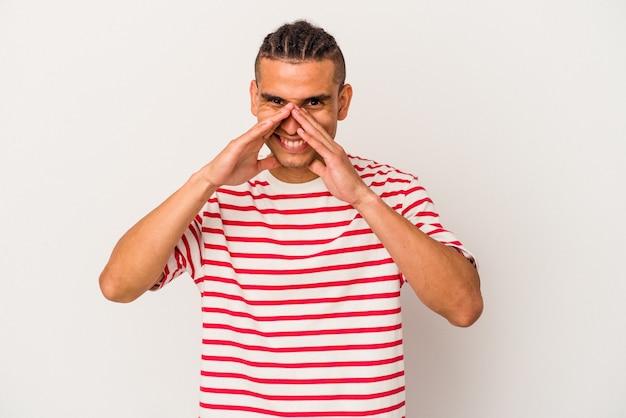 Jeune homme vénézuélien isolé sur fond blanc disant un potin, pointant vers le côté rapportant quelque chose.