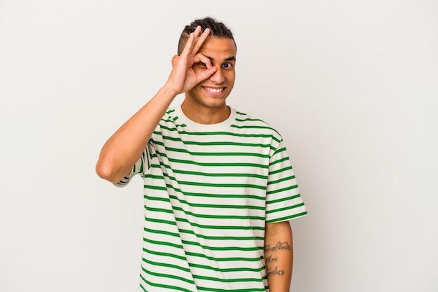 Jeune homme vénézuélien isolé sur fond blanc excité en gardant un geste ok sur les yeux.