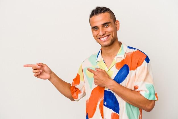 Jeune homme vénézuélien isolé sur fond blanc excité pointant avec les index loin.