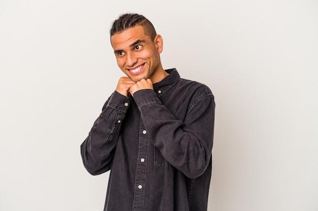 Jeune homme vénézuélien isolé sur fond blanc garde les mains sous le menton, regarde joyeusement de côté.