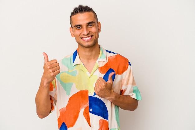 Jeune homme vénézuélien isolé sur fond blanc levant les deux pouces vers le haut, souriant et confiant.