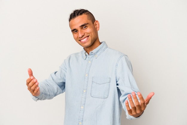 Jeune homme vénézuélien isolé sur fond blanc montrant une expression de bienvenue.