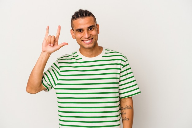 Jeune homme vénézuélien isolé sur fond blanc montrant un geste de cornes comme concept de révolution.