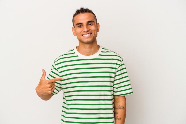 Jeune homme vénézuélien isolé sur fond blanc personne pointant à la main vers un espace de copie de chemise, fier et confiant