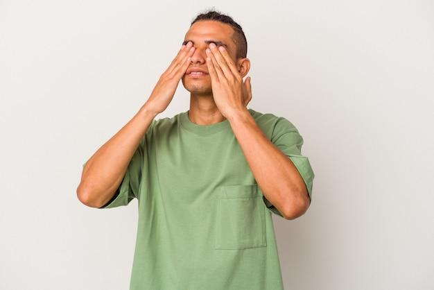Jeune homme vénézuélien isolé sur fond blanc peur couvrant les yeux avec les mains.