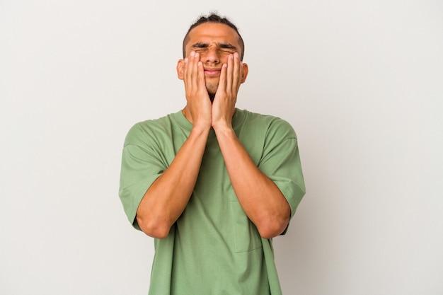 Jeune homme vénézuélien isolé sur fond blanc pleurnichant et pleurant de manière inconsolable.