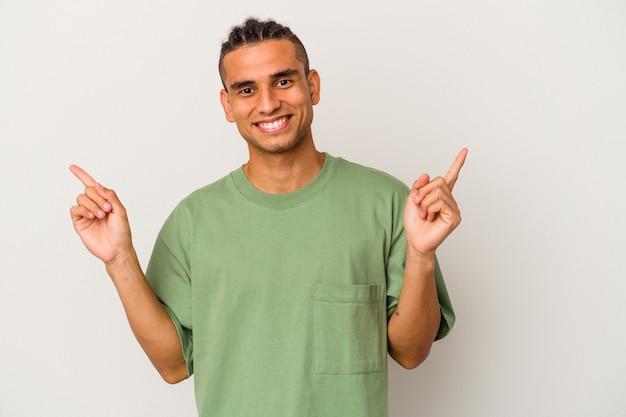 Jeune Homme Vénézuélien Isolé Sur Fond Blanc Pointant Vers Différents Espaces De Copie, En Choisissant L'un D'eux, Montrant Avec Le Doigt. Photo Premium