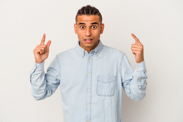 Jeune homme vénézuélien isolé sur fond blanc pointant vers le haut avec la bouche ouverte.
