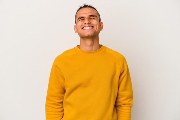 Jeune homme vénézuélien isolé sur fond blanc rit et ferme les yeux, se sent détendu et heureux.