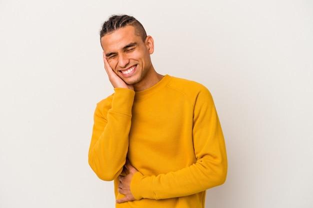 Jeune homme vénézuélien isolé sur fond blanc rit joyeusement et s'amuse en gardant les mains sur le ventre.