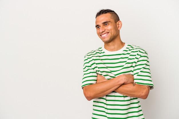 Jeune homme vénézuélien isolé sur fond blanc souriant confiant avec les bras croisés.