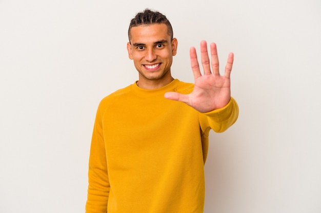 Jeune homme vénézuélien isolé sur fond blanc souriant joyeux montrant le numéro cinq avec les doigts.
