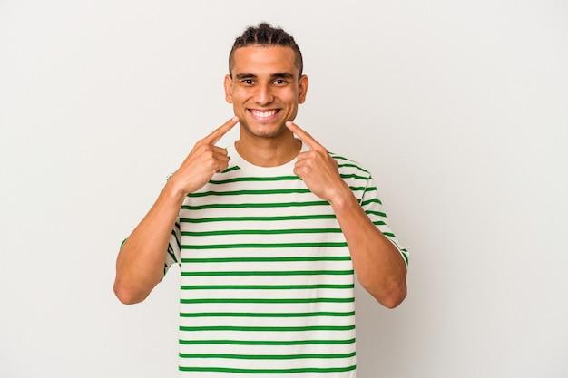 Jeune homme vénézuélien isolé sur fond blanc sourit, pointant du doigt la bouche.