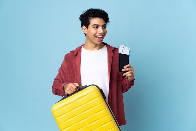 Jeune homme vénézuélien isolé sur fond bleu en vacances avec valise et passeport