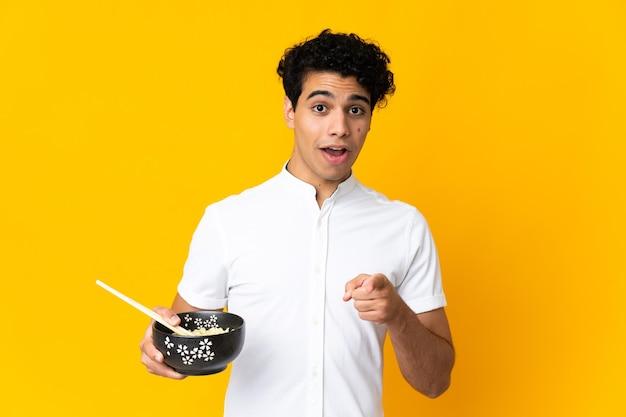 Jeune homme vénézuélien isolé sur jaune surpris et pointant vers l'avant tout en tenant un bol de nouilles avec des baguettes