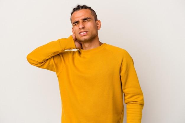 Jeune homme vénézuélien isolé sur un mur blanc ayant une douleur au cou due au stress, en le massant et en le touchant avec la main.