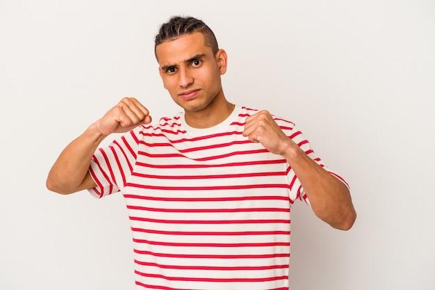 Jeune homme vénézuélien isolé sur un mur blanc jetant un coup de poing, colère, combat à cause d'une dispute, boxe.
