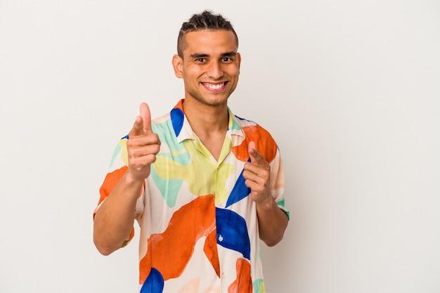 Jeune homme vénézuélien isolé sur un mur blanc pointant vers l'avant avec les doigts.