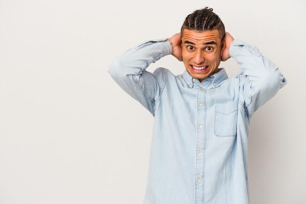 Jeune homme vénézuélien isolé sur un mur blanc touchant l'arrière de la tête, pensant et faisant un choix.