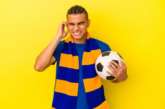 Jeune homme vénézuélien regardant le football isolé sur fond jaune couvrant les oreilles avec les mains.