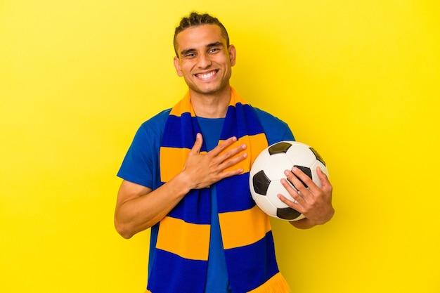 Jeune homme vénézuélien regardant le football isolé sur fond jaune éclate de rire en gardant la main sur la poitrine.