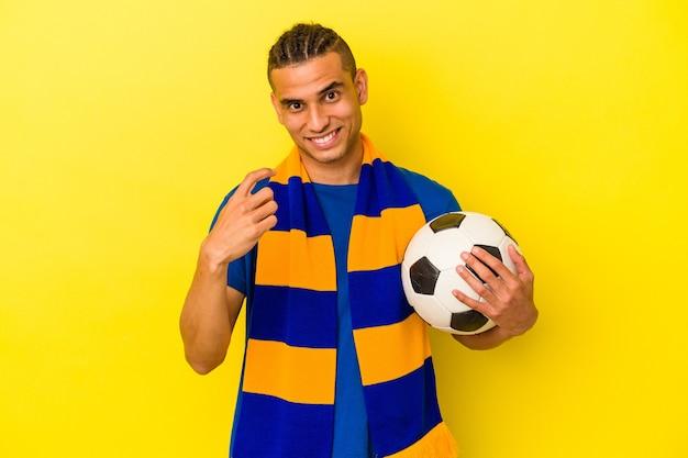 Jeune homme vénézuélien regardant le football isolé sur fond jaune pointant du doigt vers vous comme s'il vous invitait à vous rapprocher.
