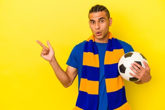 Jeune homme vénézuélien regardant le football isolé sur fond jaune pointant vers le côté