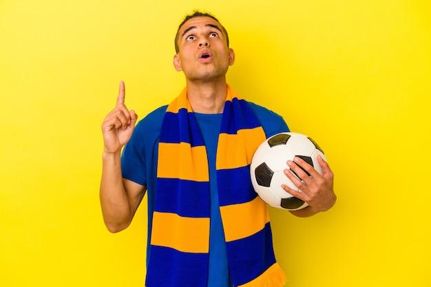 Jeune homme vénézuélien regardant le football isolé sur fond jaune pointant vers le haut avec la bouche ouverte.