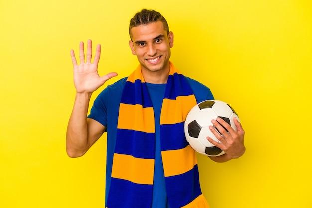 Jeune homme vénézuélien regardant le football isolé sur fond jaune souriant joyeux montrant le numéro cinq avec les doigts.