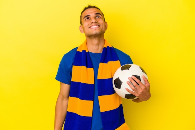 Jeune homme vénézuélien regardant le football isolé sur un mur jaune rêvant d'atteindre ses objectifs