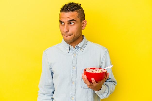 Jeune homme vénézuélien tenant un bol de céréales isolé sur fond jaune confus se sent douteux