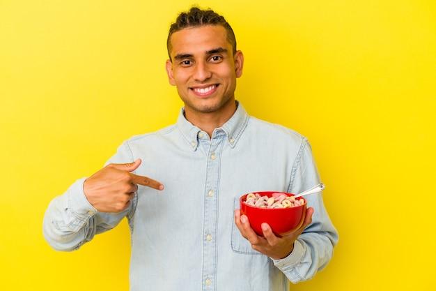Jeune homme vénézuélien tenant un bol de céréales isolé sur fond jaune personne pointant à la main vers un espace de copie de chemise, fier et confiant