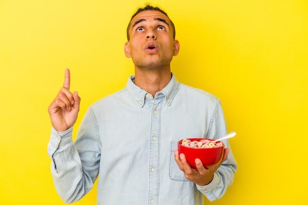 Jeune homme vénézuélien tenant un bol de céréales isolé sur fond jaune pointant