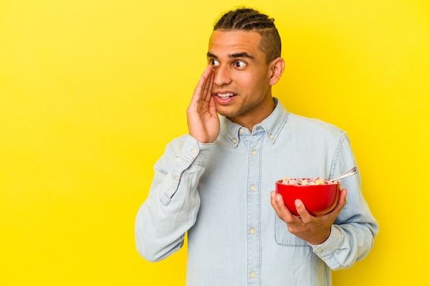 Jeune homme vénézuélien tenant un bol de céréales isolé sur fond jaune
