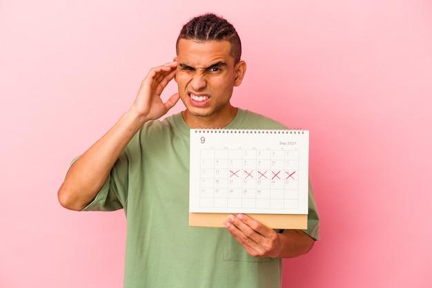 Jeune homme vénézuélien tenant un calendrier isolé sur fond rose couvrant les oreilles avec les mains.