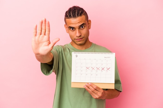 Jeune homme vénézuélien tenant un calendrier isolé sur fond rose debout avec la main tendue montrant un panneau d'arrêt, vous empêchant.