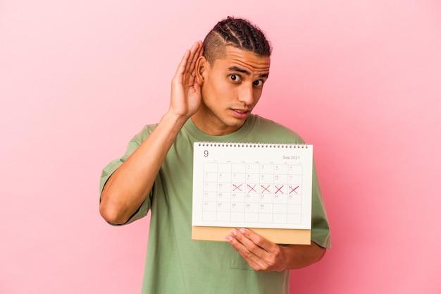 Jeune homme vénézuélien tenant un calendrier isolé sur fond rose essayant d'écouter un potin.