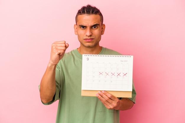 Jeune homme vénézuélien tenant un calendrier isolé sur fond rose montrant le poing à la caméra, expression faciale agressive.