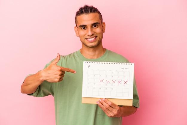 Jeune homme vénézuélien tenant un calendrier isolé sur fond rose personne pointant à la main vers un espace de copie de chemise, fier et confiant